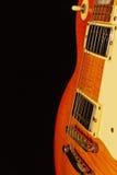 在黑背景的蜂蜜镶有钻石的旭日形首饰的电蓝色吉他特写镜头 浅深度的域 免版税库存照片