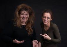 在黑背景的醉酒的两名妇女 图库摄影