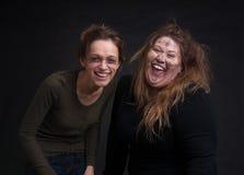 在黑背景的醉酒的两名妇女 库存图片