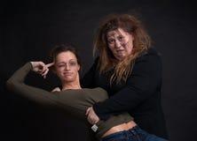 在黑背景的醉酒的两名妇女 免版税库存图片