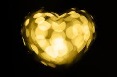 在黑背景的金黄bokeh心脏 库存照片