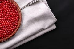 在黑背景的饱和的红浆果 充分篮子在一块灰色布料的红浆果 健康饭食的土气莓果 库存照片