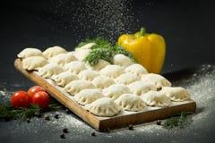 在黑背景的饺子用新鲜的草本和菜 是可能食物自创饼 传统俄国食物是pelmeni 免版税库存照片