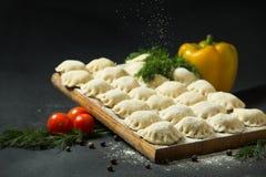 在黑背景的饺子用新鲜的草本和菜 是可能食物自创饼 传统俄国食物是pelmeni 免版税库存图片