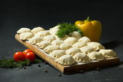 在黑背景的饺子用新鲜的草本和菜 是可能食物自创饼 传统俄国食物是pelmeni 图库摄影
