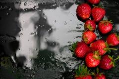 在黑背景的整个草莓用水滴下 湿 框架,拷贝空间 顶视图 免版税库存图片