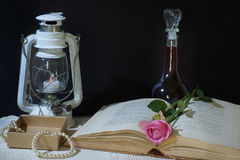 在黑背景的水平的静物画与书、一个老灯笼和一个瓶酒,桃红色上升了谎言在页之间, 库存图片