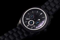 在黑背景的黑手表 免版税库存照片
