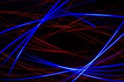 在黑背景的轻的螺旋,红色和蓝线 库存图片