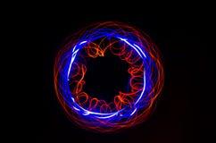 在黑背景的轻的螺旋,红色和蓝线 库存照片