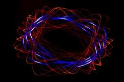 在黑背景的轻的螺旋,红色和蓝线 免版税库存照片