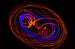 在黑背景的轻的螺旋,红色和蓝线 免版税库存图片