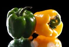 在黑背景的绿色和黄色甜椒 免版税库存照片