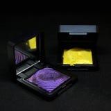 在黑背景的紫色和黄色眼影膏 库存照片