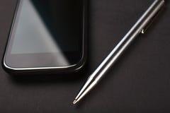 在黑背景的Smartphone和笔 免版税库存照片