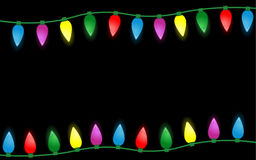 在黑背景隔绝的五颜六色的圣诞灯边界 免版税库存照片