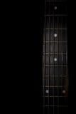 在黑背景隔绝的吉他脖子 免版税库存照片