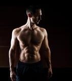 在黑背景隔绝的肌肉英俊的人 库存图片