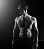 在黑背景隔绝的肌肉英俊的人 免版税库存照片