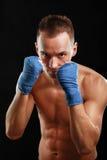 在黑背景隔绝的年轻拳击手人 免版税图库摄影