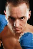 在黑背景隔绝的年轻拳击手人 库存图片