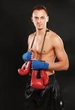 在黑背景隔绝的年轻拳击手人 免版税库存图片