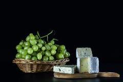 在黑背景青纹干酪和白葡萄的构成在一个柳条筐 免版税库存图片