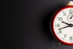 在黑背景,时间概念,仓促的红色闹钟 库存照片