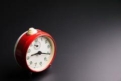 在黑背景,时间概念,仓促的红色闹钟 图库摄影