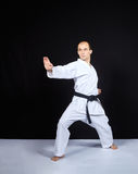 在黑背景, karategi的一位运动员训练一个块用他的手 免版税库存照片