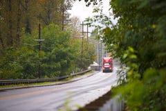 在绿色下雨的路的红色现代半卡车whith光 免版税图库摄影