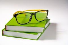 在绿色书的玻璃 免版税库存照片