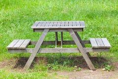 在绿色公园的木长凳在夏天 免版税库存图片
