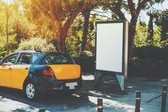 在黄色出租汽车附近的空白的广告牌 免版税库存照片