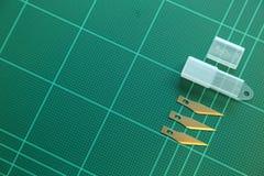 在绿色切板的切削刀 免版税库存图片