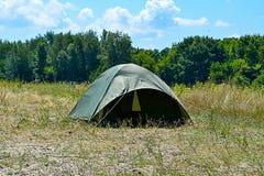 在绿色前面、蓝天和太阳的旅游帐篷 免版税库存照片