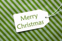 在绿色包装纸,文本圣诞快乐的标签 免版税库存图片
