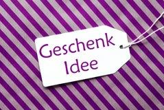 在紫色包装纸, Geschenk Idee的标签意味礼物想法 库存照片