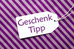 在紫色包装纸, Geschenk Tipp的标签意味礼物技巧 图库摄影