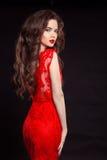 在黑色后面隔绝的红色时尚礼服的美丽的性感的妇女 免版税库存照片