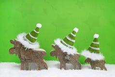在绿色和白色木圣诞节背景w的驯鹿家庭 免版税库存照片