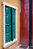在黄色和红色墙壁上的绿色木窗口 免版税库存照片