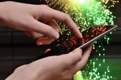 在绿色和红色背景的手感人的巧妙的电话 免版税库存图片