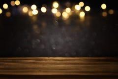 在黑色和金子闪烁前面的空的桌点燃背景