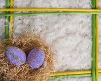 在黄色和绿色木制框架的两个复活节彩蛋 免版税图库摄影