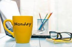 在黄色咖啡或茶杯写的星期一在木板桌,工作场所,办公室阳光早晨背景上 库存照片