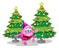 在绿色圣诞树附近的一个桃红色童帽妖怪 免版税库存照片
