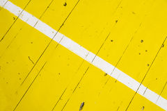 在黄色地板上的白色条纹 免版税库存照片