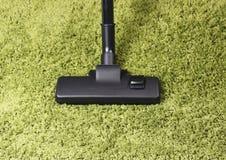 在绿色地毯的吸尘器 免版税库存图片