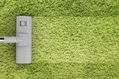 在绿色地毯的真空清洁 库存照片